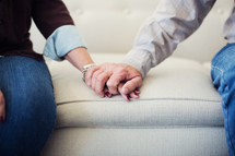 mature couple holding hands on a couch.