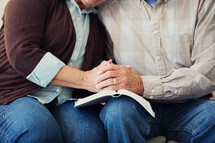 A mature couple praying together over the open pages of a Bible.