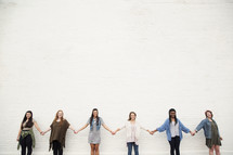 Six young women holding hands in a line.
