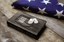 Folded American flag, dog tags, and Bible