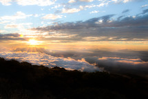 morning clouds at sunrise above mountain peaks