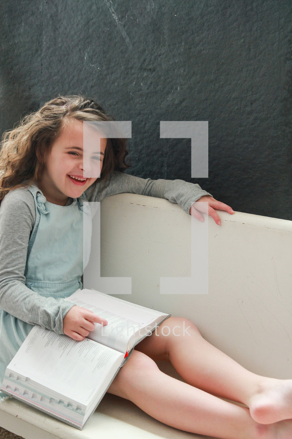 Happy girl reading her Bible on a bench.