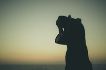 silhouette of a man in robe pulling his hair