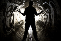 Silhouette of man straddling water flowing through a graffiti-painted sewer drain pipe with arms extended.