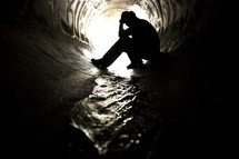 Silhouette of man sitting with head in hands in a graffiti-painted sewer drain pipe with water flowing through it.