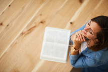 a woman praying and an open Bible