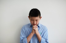 boy with head bowed in prayer
