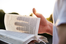 a woman turning the pages of a Bible outdoors in sunlight