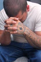 tattooed hands in prayer