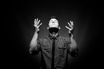 man with raised hands and his head tilted to God in worship and praise