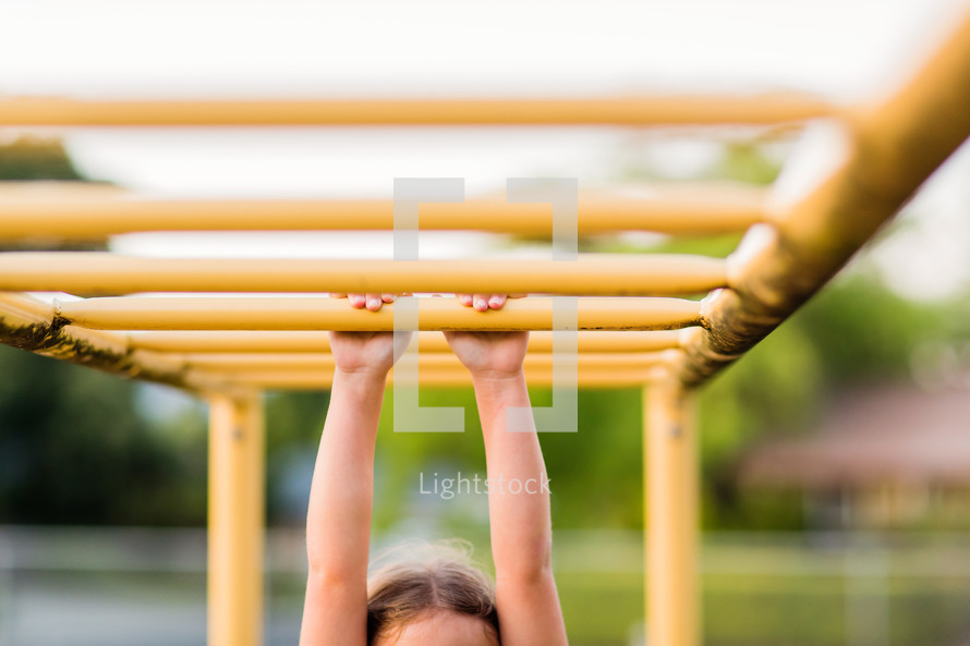 Child, young girl, hanging from bars, playground, hang in there, hold tight, grasp, play, monkey bars