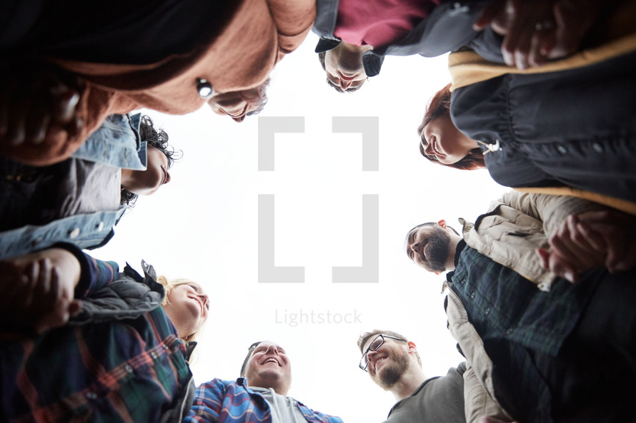looking up into a group prayer circle with men and women holding hands in prayer in fall