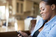 Smiling woman texting while sitting on a sofa.