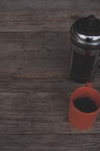 A french press and orange coffee mug