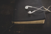 White ear buds on a Bible