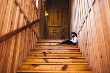 A boy sits on a wooden stairway.