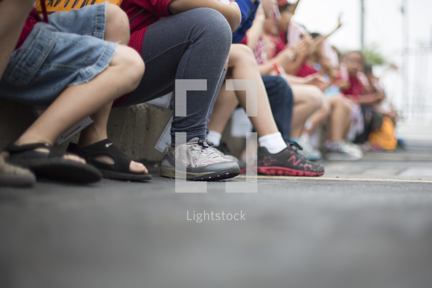 children sitting on the curb
