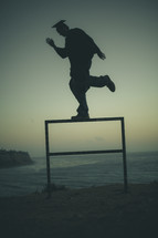 graduate balancing on a beach