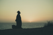 silhouette of a graduate on a beach kneeling in prayer