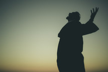 silhouette of a man with his arms raised