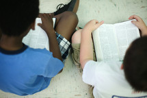 children sitting reading Bibles