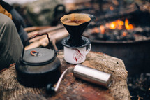 coffee grinder and slow brew coffee by a fire