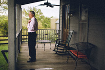 man buttoning a shirt on a porch