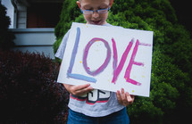 a boy holding a sign with the word love