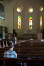 woman in prayer in an empty church