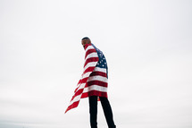 A man wrapped in an American flag.