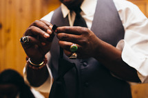 A man in a tie and vest with many rings on his fingers.