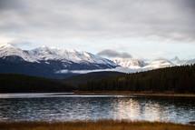 snow capped mountain peaks across a lake