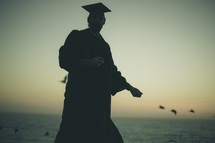 silhouette of a graduate on a beach