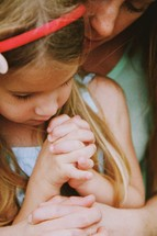little girl praying being held by her mother