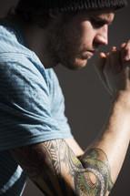 Tattooed man in prayer.