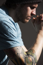 Tattooed man in prayer.