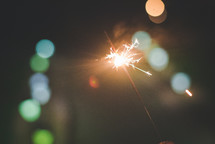 holding a sparkler and bokeh lights
