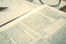 reading glasses, pen, and open Bible
