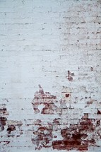 Delapidated, white-washed brick wall.