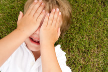 child cover his face lying in the grass