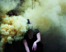 a woman sitting in smoke