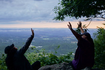 friends with raised hands sitting at the edge of a cliff on a mountaintop