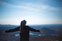 woman standing on a mountaintop with outstretched arms