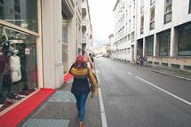 women window shopping walking down a street in Europe