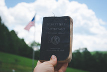holding up a Bible in front of an American flag
