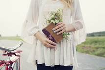 woman holding a journal and flowers standing next to a bike