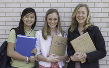 Smiling teens with text books at school.