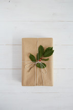 holly and gift on a white wood background