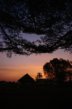silhouettes of huts sunset in an African village