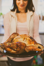 a woman holding a roasted turkey